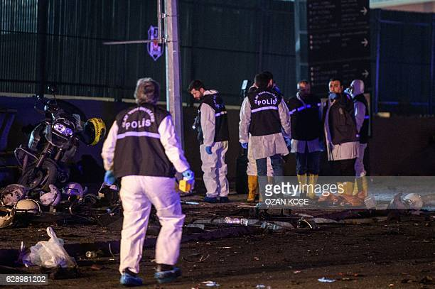 Turkish forensic police officers work on the site where a car bomb exploded near the stadium of football club Besiktas in central Istanbul on...