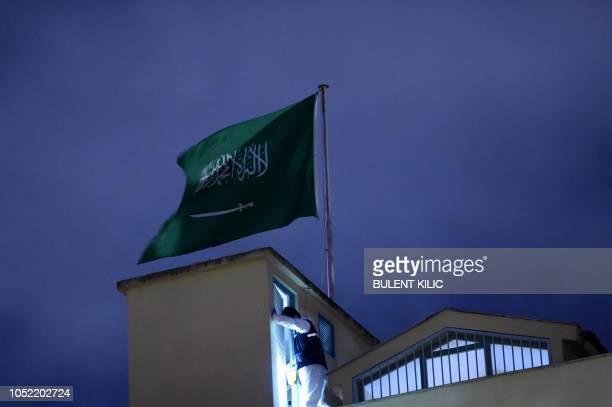 A Turkish forensic stands next to the Saudi flag on the roof of the Saudi Arabia's consulate in Istanbul on October 15 2018 during the investigation...