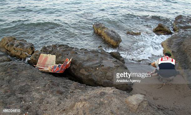 Turkish gendarmerie soldier moves the body of a migrant washed ashore on a beach after a boat carrying 12 migrants sank off the coast of Mugla's...