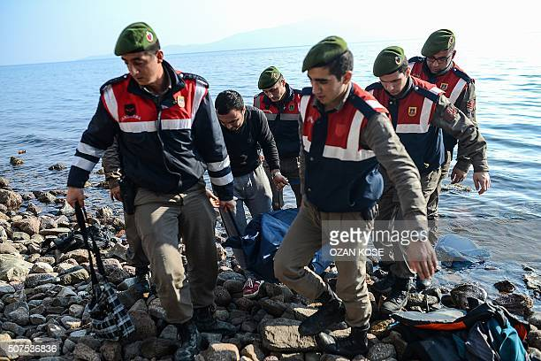TOPSHOT Turkish gendarmes carry the body of a migrant on a beach in Canakkale's Bademli district on January 30 2016 after at least 33 migrants...
