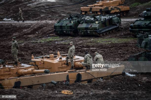 Turkish Germanmade Leopard 2A4 battle tanks are stationed in a field near the Syrian border at Hassa in Hatay province on January 25 as part of the...