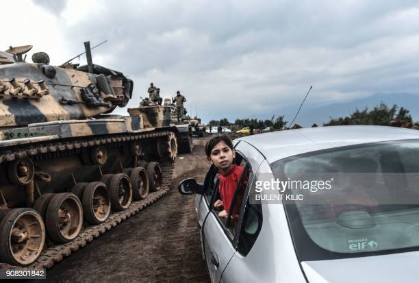 TOPSHOT A Turkish girl leans out of a car window to have a look as Turkish army tanks and soldiers gather close to the Syrian border at Hassa in...