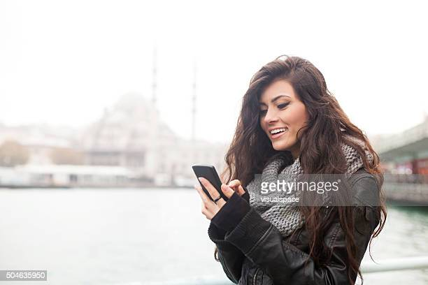 Turkish Girl Texting On Smartphone Outdoors In Istanbul