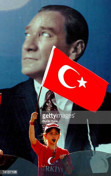 A Turkish girl waves her flag in front of Ataturk poster founder of modern Turkey during an antigovernment rally on May 13 2007 in Turkey's western...