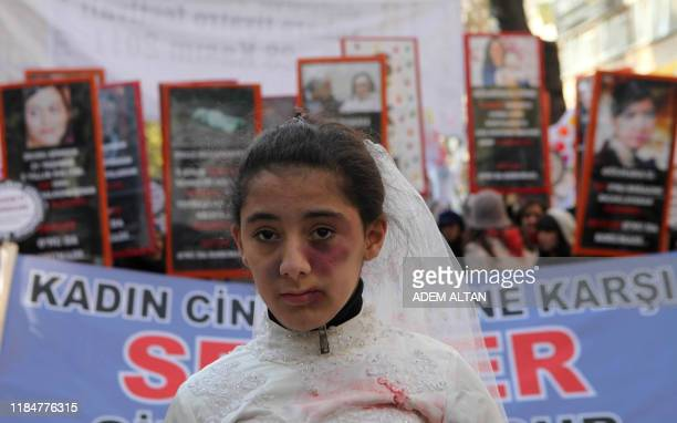 A Turkish girl wearing a wedding dress and covered with fake bruises stands in front of other protesters holding placard reading '' end violence''...