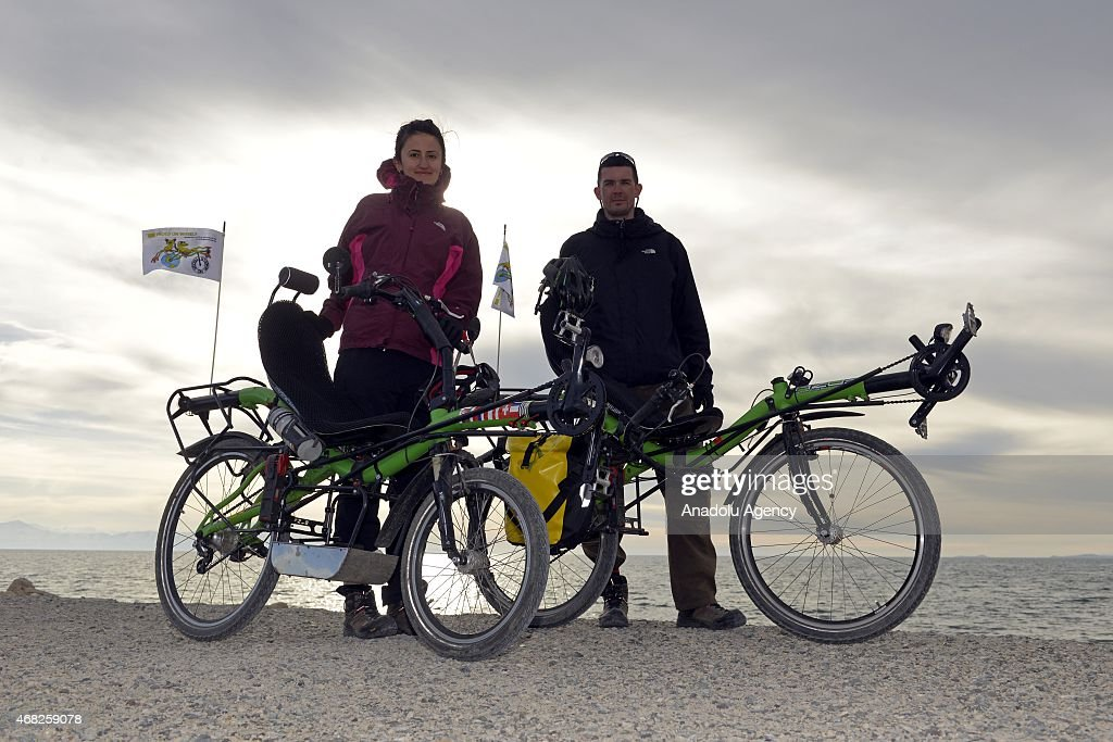 Turkish Gokben Bagci and her French husband Nicolas Ayme pose for photographers as they tour the world on March 27, 2015 in Van, eastern Turkey. The couple plans to travel around the world on their recumbent bikes for 4 years.