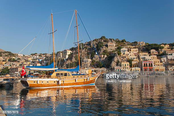 turkish gulet in the harbour, gialos, symi, greece - symi stock photos and pictures