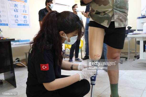 Turkish health worker puts on a prosthesis leg at a physiotherapy and rehabilitation in Tal Abyad district which was cleared from PKK, listed as a...