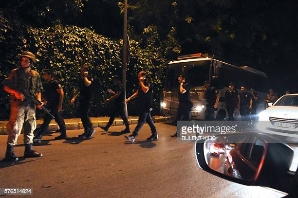 Turkish internal security officers pass a Turkish soldier on July 15, 2016 in Istanbul, during a security shutdown of the Bosphorus Bridge. Turkish...