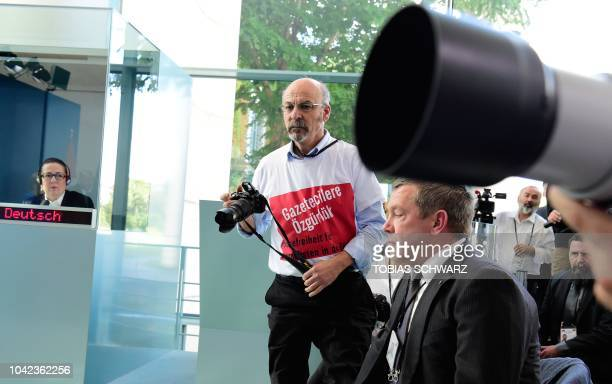 Turkish journalist Ertugrul Yigit wears a shirt reading Freedom for journalists Freedom of the press for journalists in Turkey during a joint press...