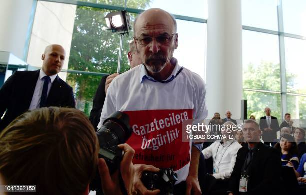 Turkish journalist Ertugrul Yigit who has written Freedom for journalists Freedom of the press for journalists in Turkey on his shirt is led out of...