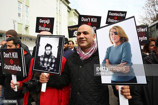 A Turkish journalist in Ankara on February 24 holds pictures of two journalists French photojournalist Remi Ochlik and Sunday Times correspondent...