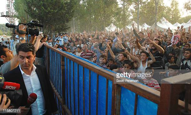 Turkish journalist watches as Syrian refugees rally against Syrian President Bashar al-Assad at their camp on June 10, 2011 in the border town of...