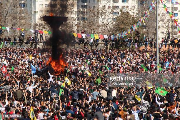 Turkish Kurds gather around a bonfire during Newroz celebrations for the new year in Diyarbakir, southeastern Turkey, on March 21, 2019. - Newroz is...