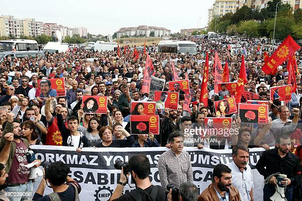 Turkish Labour Party activists chant slogans as they display placards during a demonstration in Ankara on October 11 featuring images of party...