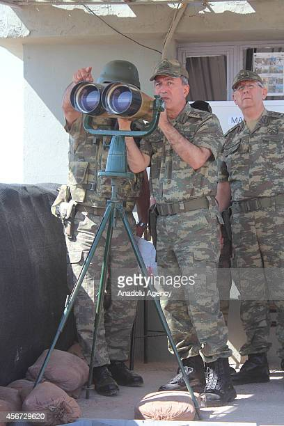 Turkish Land Forces Commander General Hulusi Akar appraises the situation on the Syrian border looking out onto Ayn alArab city through binoculars as...