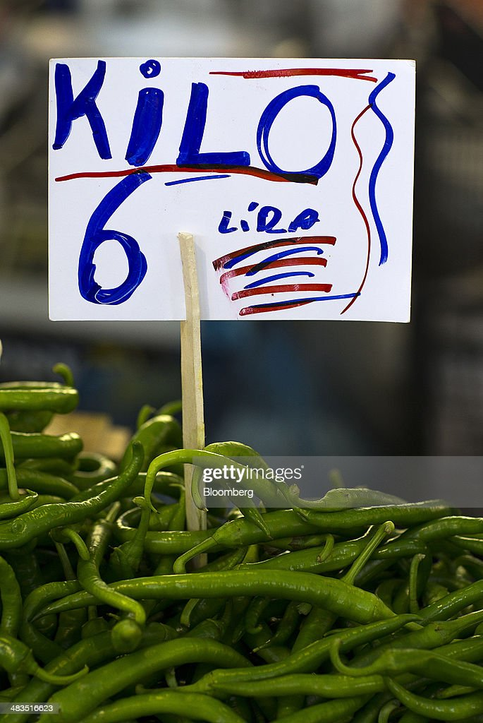A Turkish lira price sign stands above a display of green peppers for sale at a stall in the Yesilkoy street market in Istanbul, Turkey, on Wednesday, April 9, 2014. Turkish central bank Governor Erdem Basci indicated to analysts in London on April 3 that he planned to keep monetary policy tight to control inflation. Photographer: Kerim Okten/Bloomberg via Getty Images