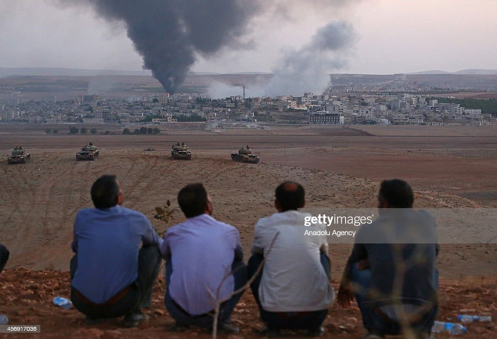 Turkish local residents watch the smoke rising from Syria's Ayn al-Arab city (Kobani) after the shelling at the clashes between the Islamic State of Iraq and the Levant (ISIL) and Kurdish armed groups in Ayn al-Arab city on October 9, 2014.