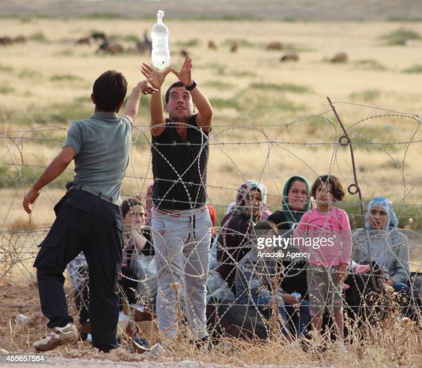 Turkish man distributes drinking water to Syrians, fled from clashes between the Islamic State of Iraq and Levant militants and Democratic Union...