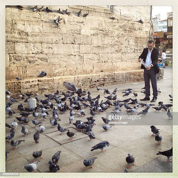 Turkish man feeding doves