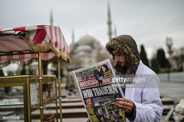 A Turkish man holds a Turkish newspaper with a title in German which translates as We mourn in front of the Blue Mosque near the explosion scane in...
