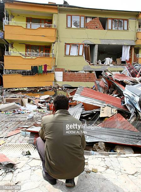 A Turkish man looks at the rubbles of collapsed buildings in Ercis on October 26 after a major earthquake of 72 magnitude hit eastern province of Van...
