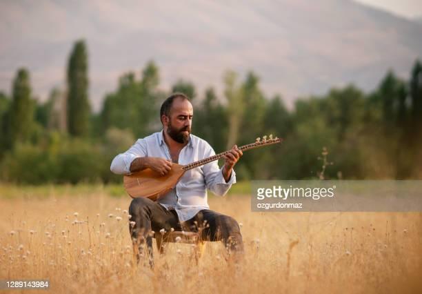 turkish man playing baglama (saz) turkish musical instrument - folk music stock pictures, royalty-free photos & images