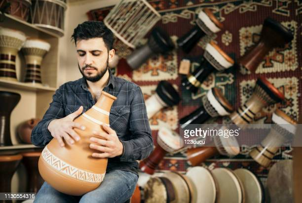 turkish man playing clay darbuka - vaso de barro imagens e fotografias de stock