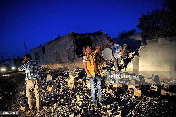 Turkish man stands amongst rubble as he and others inspect a house that was damaged during attacks by Islamic State which saw IS fighters shoot into...