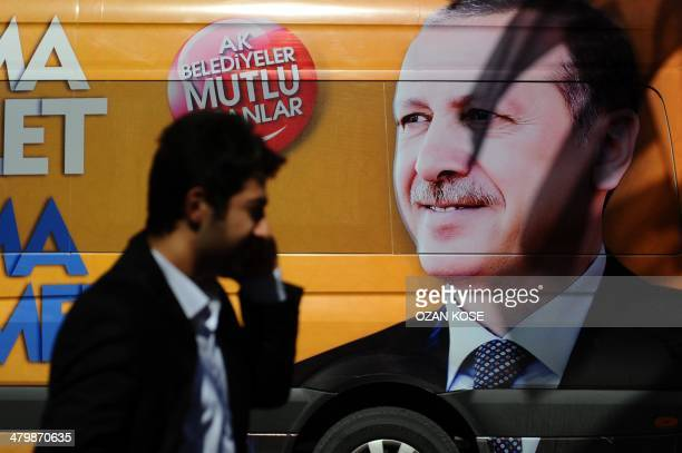 A Turkish man talks on the phone as he walks in front of a poster displaying a portrait of Turkish prime minister Recep Tayyip Erdogan in Istanbul on...