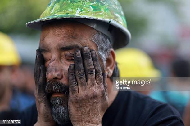 Turkish man wearing a miner's helmet and stains his face with coal during a protest in front of the Turkish policemen at a street near Taksim Square,...