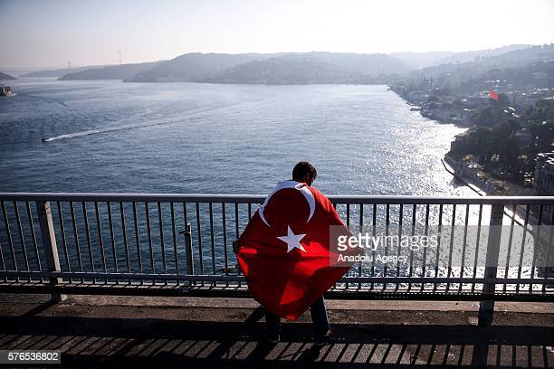 Turkish man with a flag is seen after a group of soldiers with armored vehicle involved in 'Parallel State/Gulenist Terrorist Organization's coup...