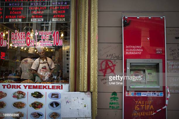 Turkish man works in a resturant next to an ATM machine that was damaged during riots after antigovernment demonstrations on June 5 2013 in Istanbul...