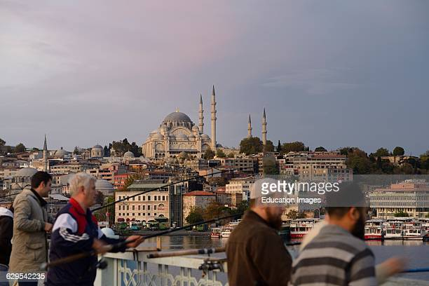 Turkish men fishing on Galata Bridge over Golden Horn with Suleymaniye Mosque Istanbul