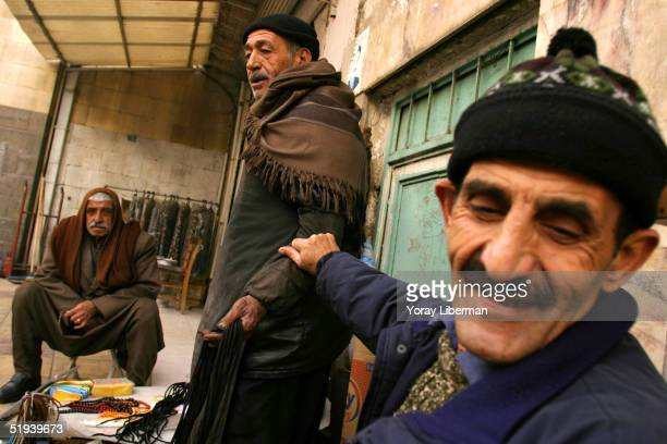 Turkish men sit in the street in the early morning selling shoelaces December 4 2004 in Gaziantep Turkey Small businesses are very common on the...