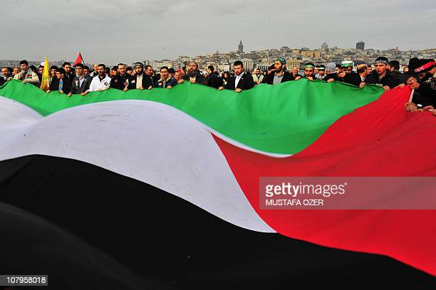 Turkish men wave a giant Palestinian flag during the arrival of Turkish ship Mavi Marmara at Istanbul's Sarayburnu port on December 26 2010 The...