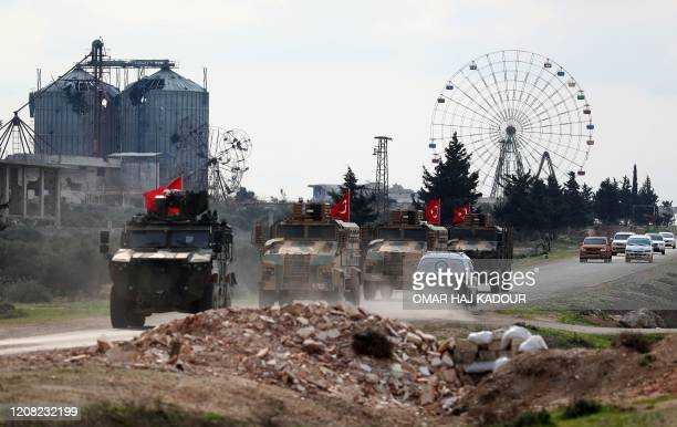 Turkish military convoy drives along the M4 highway, which links the northern Syrian provinces of Aleppo and Latakia, near the village of al-Nayrab,...
