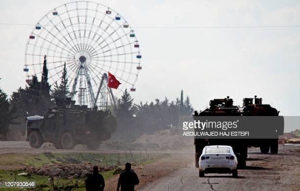 Turkish military convoy drives on M4 highway, which links the northern Syrian provinces of Aleppo and Latakia, near the village of al-Nayrab, about...