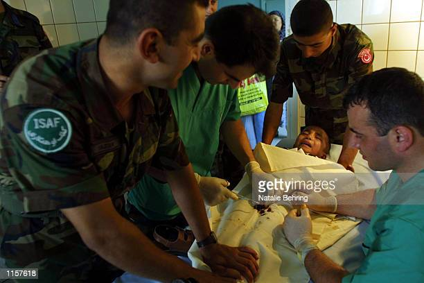 Turkish Military doctors taking part in Kabul's International Security and Assistance Force restrain a young boy undergoing a circumcision in Kabul...