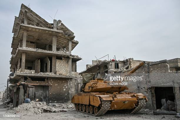 A Turkish military tank is seen in a destroyed neighbourhood of Sarmin town about eight kilometres southeast of the city of Idlib in northwestern...