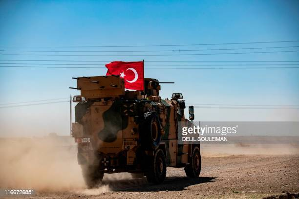 A Turkish military vehicle drives on a joint patrol with US troops in the Syrian village of alHashisha on the outskirts of Tal Abyad town on the...