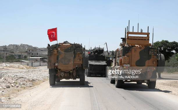 Turkish military vehicles accompany a towed damaged vehicle the site of an improvised explosive device which hit a joint Turkish-Russian patrol on...