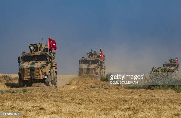 Turkish military vehicles part of a US military convoy take part in joint patrol in the Syrian village of alHashisha on the outskirts of Tal Abyad...