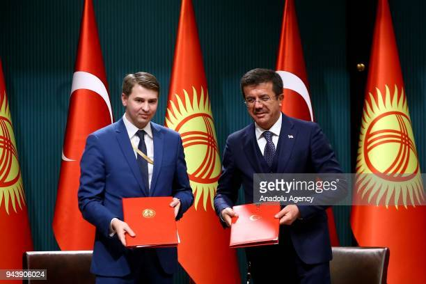 Turkish Minister of Economy Nihat Zeybekci and his Kyrgyz counterpart Artem Novikov pose for a photo after signing cooperation agreements between two...