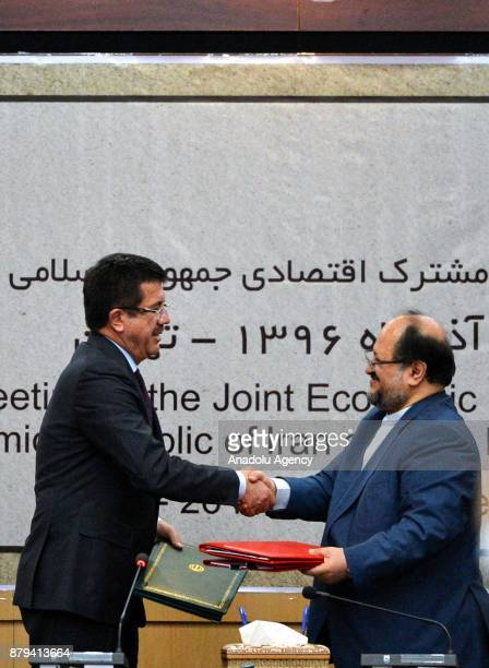 Turkish Minister of Economy Nihat Zeybekci and Iranian Minister of Industry Mine and Trade Mohammad Shariatmadari shake their hands after signing the...