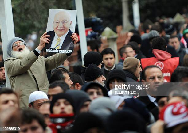 A Turkish Muslim man holds up a picture of former Prime Minister Necmettin Erbakan during his funeral in Istanbul on March 1 2011 Tens of thousands...