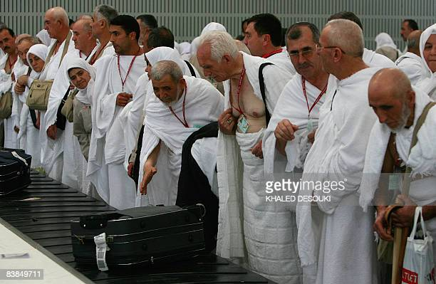 Turkish Muslim pilgrims wait next to a luggage belt to pick up their suitcases upon their arrival to King Abdul Aziz airport in the Red Sea port city...
