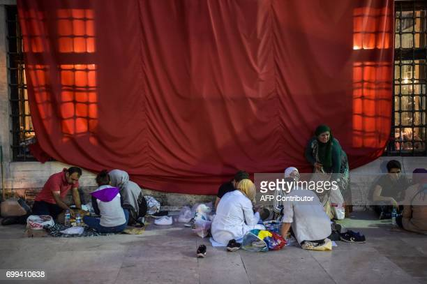 Turkish Muslim worshippers break their fast next to a Turkish national flag on June 21 2017 outside the Eyup Sultan mosque on the occasion of Laylat...