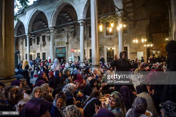 Turkish Muslim worshippers break their fast on June 21 2017 outside the Eyup Sultan mosque on the occasion of Laylat alQadr which falls on the 27th...
