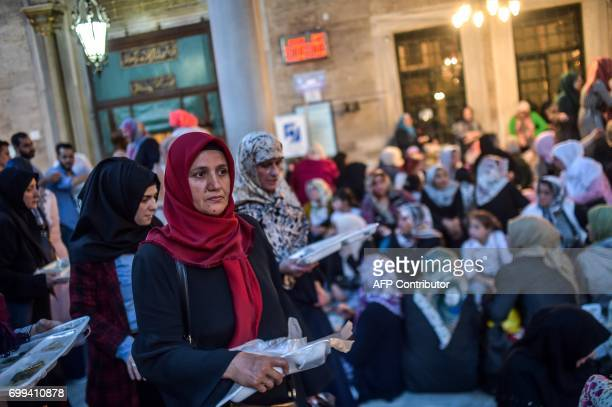 Turkish Muslim worshippers prepare their food to break their fast on June 21 2017 outside the Eyup Sultan mosque on the occasion of Laylat alQadr...